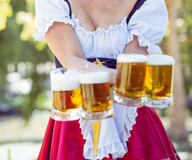 pretty-oktoberfest-blonde-holding-beers-on-a-sunny-PCYD5G9.jpg