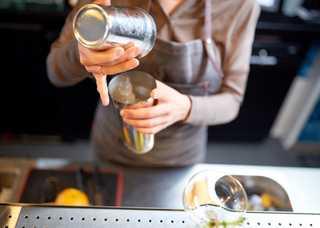 woman-bartender-with-cocktail-shaker-at-bar-PC9JVE4.jpg
